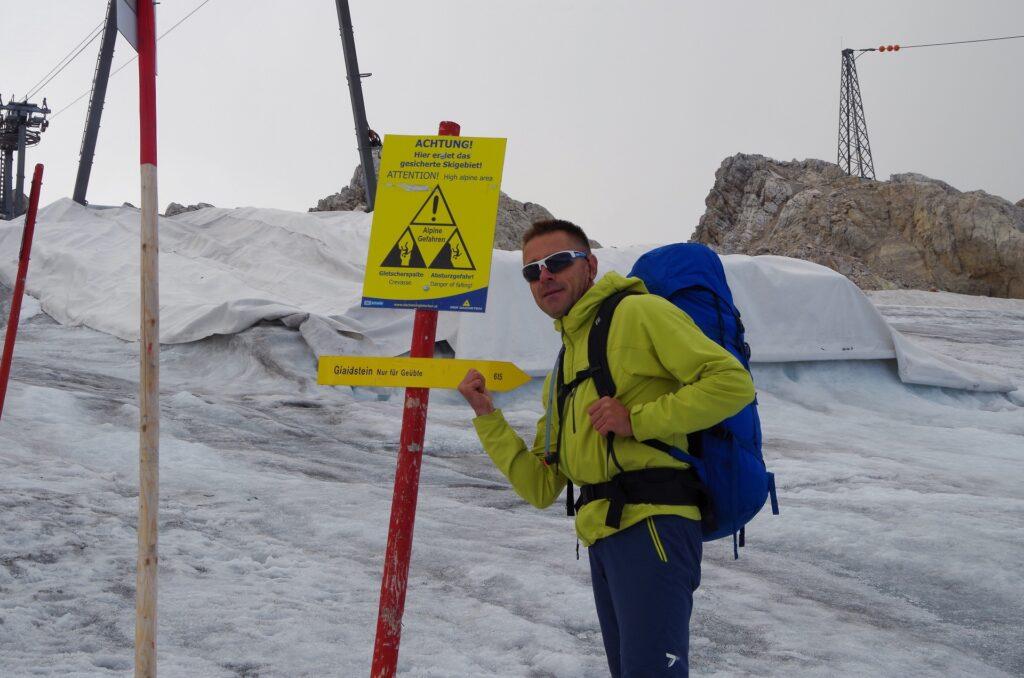Darek przy tablicy ostrzegawczej o lodowcu